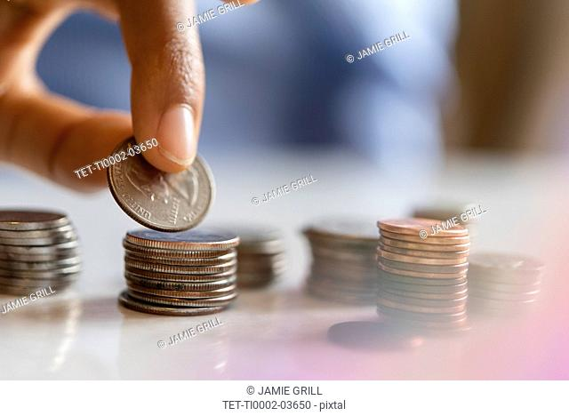 Hand of woman stacking coins