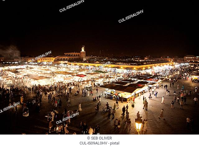 Crowds of shoppers and market stalls at night, Jamaa el Fna Square, Marrakech, Morocco