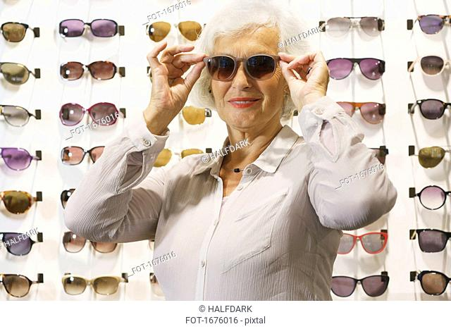 Smiling senior woman wearing sunglasses while standing at store