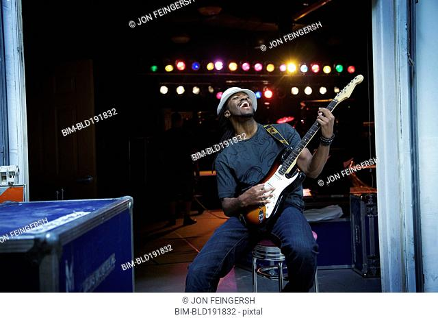 African man playing electric guitar backstage