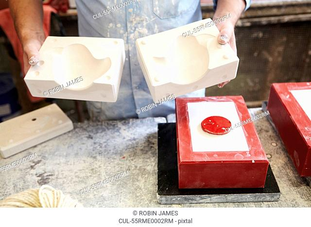 Man holding plaster cast mould in pottery factory