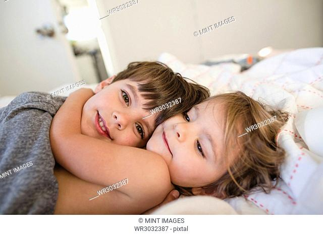 Smiling boy with brown hair and young girl lying on a bed, hugging