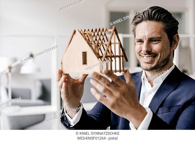Smiling architect examining architectural model