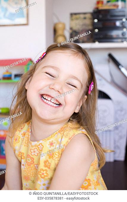 portrait of three years old blonde pretty girl face, with yellow dress, llaughing with closed eyes