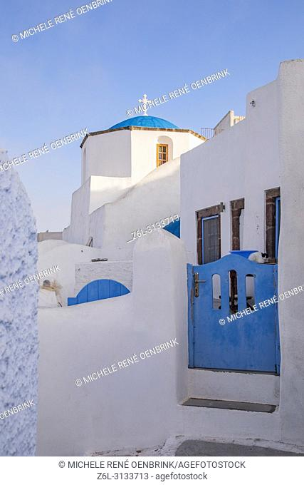 Traditional blue domed Greek Orthodox church with steeple and cross in Pyrgos, Santorini Greece