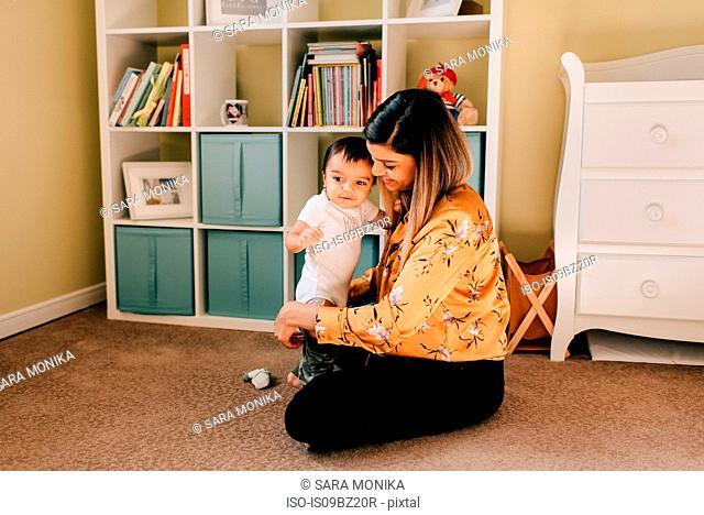 Mother sitting on nursery floor dressing baby son