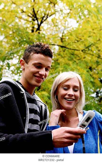 teenage couple, watching, cellular phone, young ad