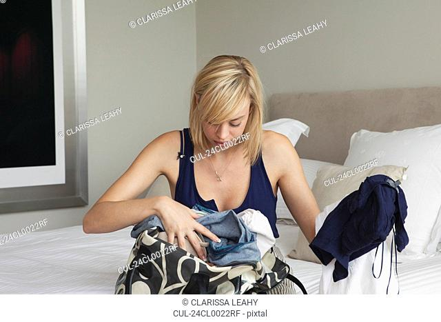 Woman sorting through clothes in bag