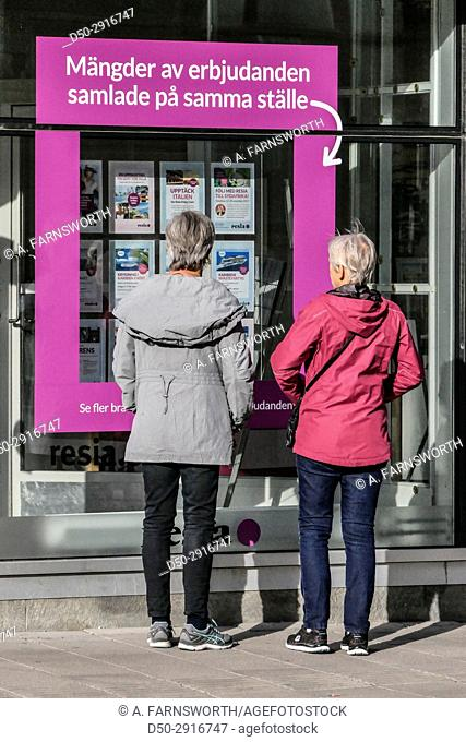 UPPSALA, SWEDEN Central station. Women look at travel advertisements