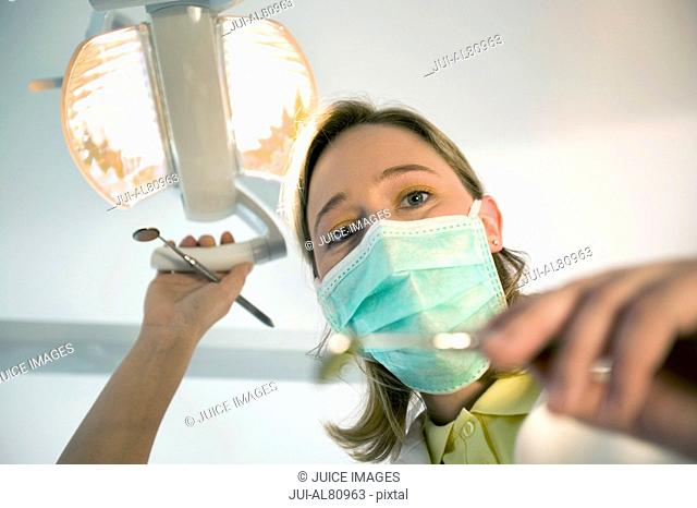Female dentist wearing surgical mask and holding dental tools