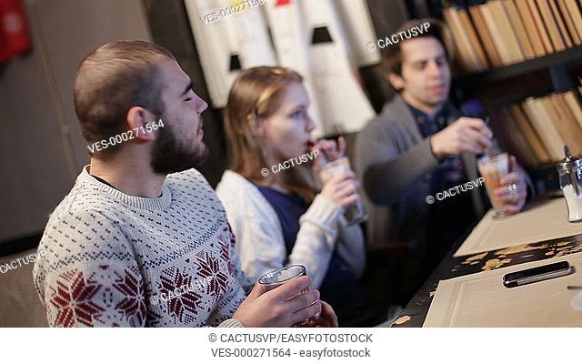 Joyful teenage friends relaxing in coffee shop