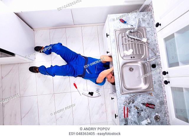 Male Plumber Lying On Floor Fixing Pipe Into Sink In Kitchen