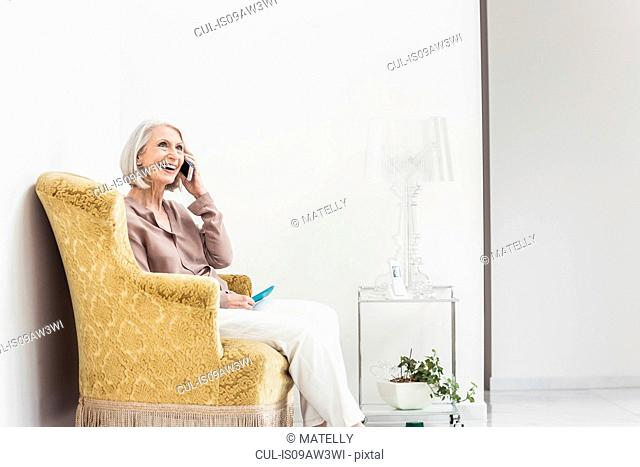 Senior woman at home, sitting in chair, using smartphone