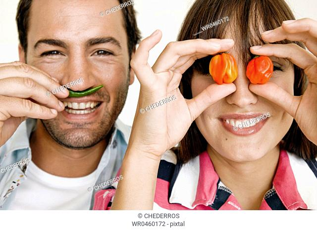 Close-up of a young woman holding two bell peppers in front of her eyes and a young man with a green chili pepper on his lips