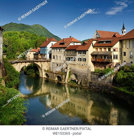 Stone Capuchin bridge with statue of St John of Nepomuk with historic houses reflected in the Selca Sora river in Skofja Loka village Slovenia