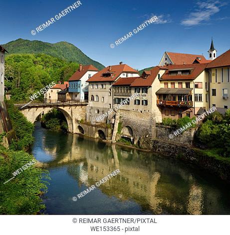 Stone Capuchin bridge with statue of St John of Nepomuk with historic houses reflected in the Selca Sora river in Skofja Loka village Slovenia