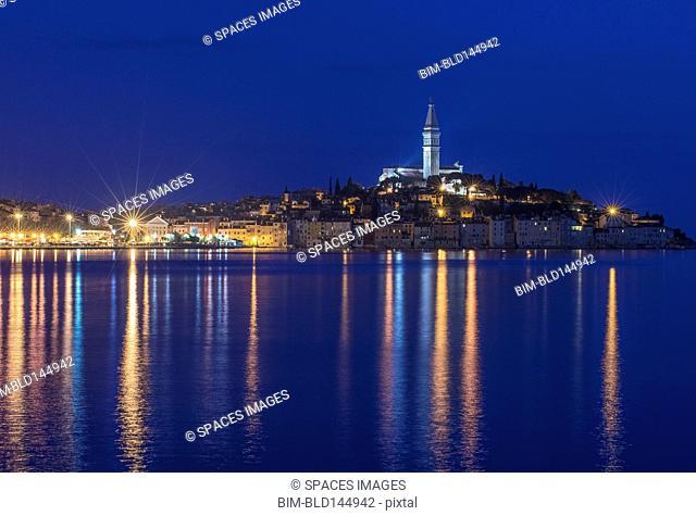 Illuminated coastal city reflected in still water, Rovinj, Istria, Croatia