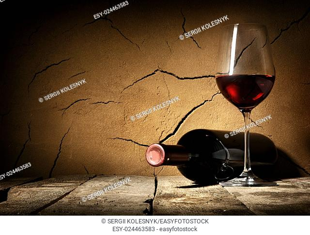 Wine and cracked clay wall in cellar