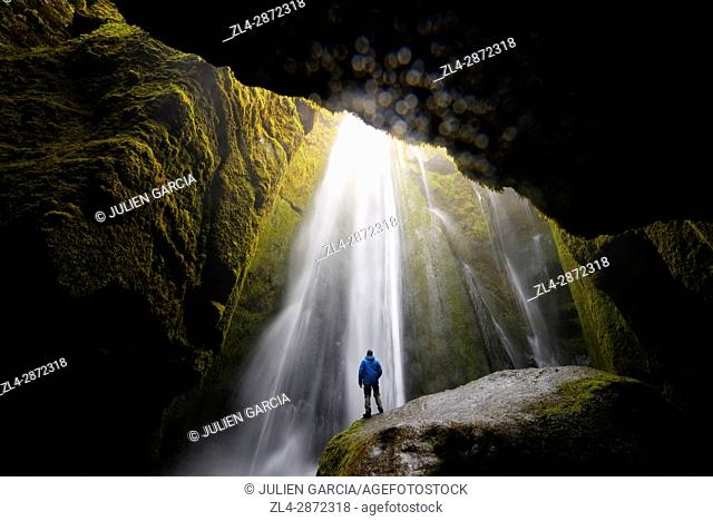 Iceland, Sudurland region, hiker standing on a rock in front of Gljufrafoss waterfall, Model Released