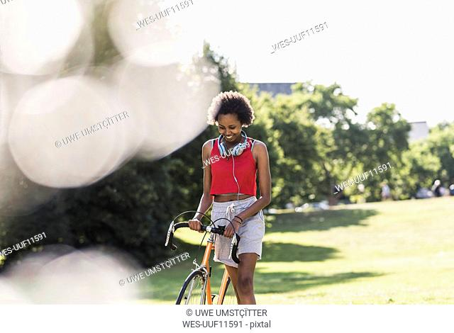 Smiling sporty young woman pushing bicycle in park
