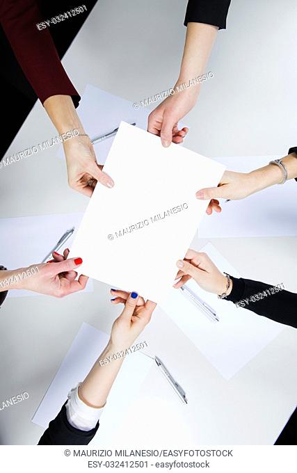 In the office, a workgroup composed of five women in a circle holding a blank sheet above a desk