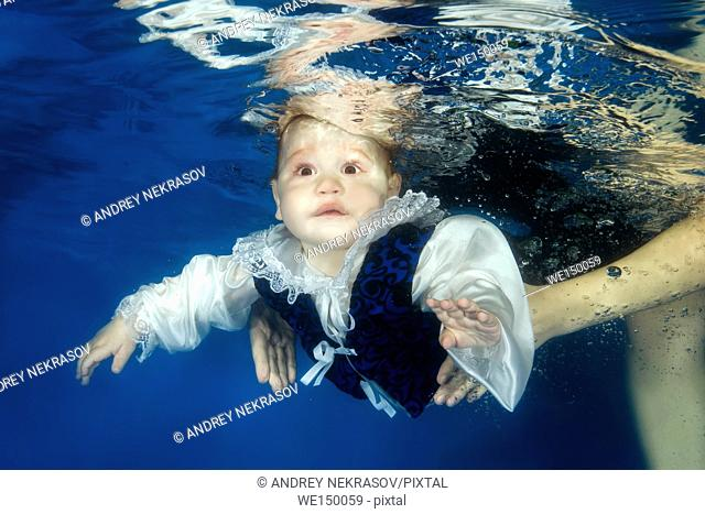 Little boy in the little prince's suit posing under the water in the pool