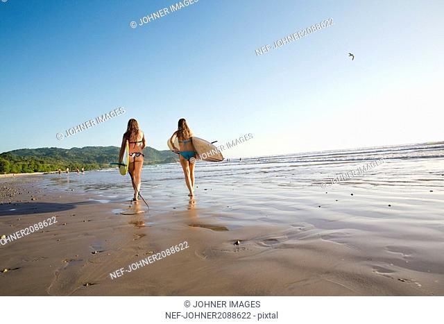 Teenage girls walking on beach with surfboards