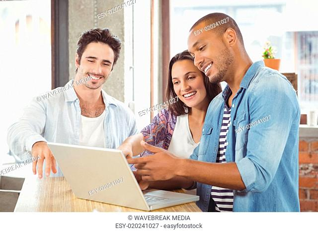 Happy business people pointing towards laptop in office