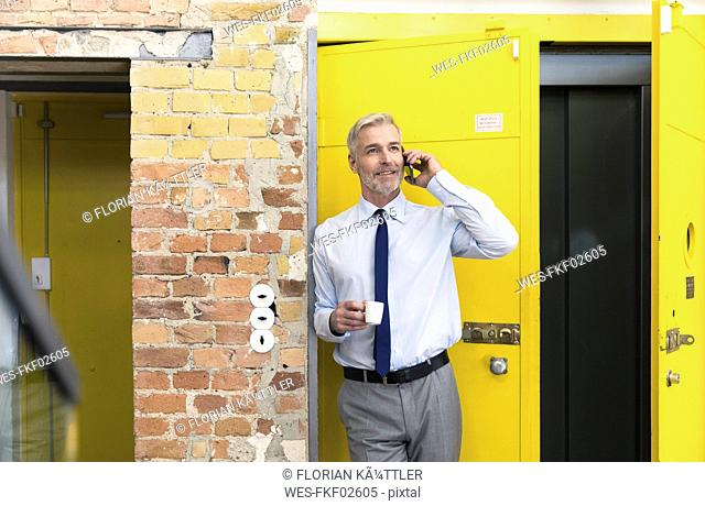 Businessman leaning in front of elevator using smartphone, drinking coffee