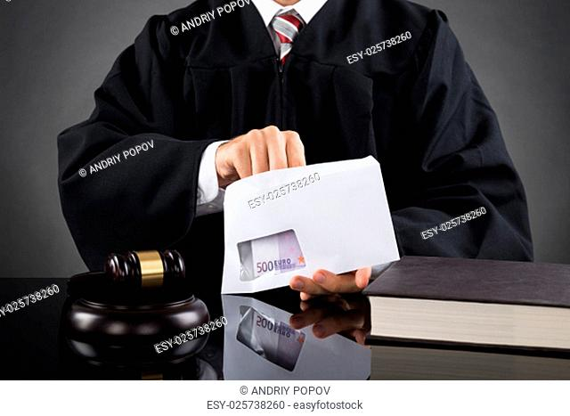 Close-up Of Judge Putting Money In Envelope At Desk In Courtroom