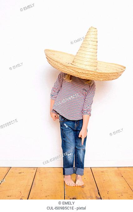 Young girl, wearing sombrero, pointing to feet