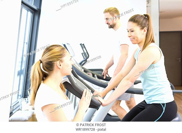 Physiotherapist helping patients with cycles in gym