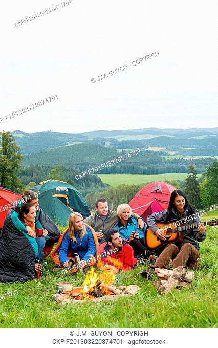 Group of friends sitting beside tents, campfire girl playing guitar