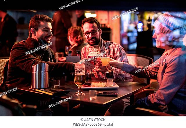 Three friends at a pub at night clinking beer glasses