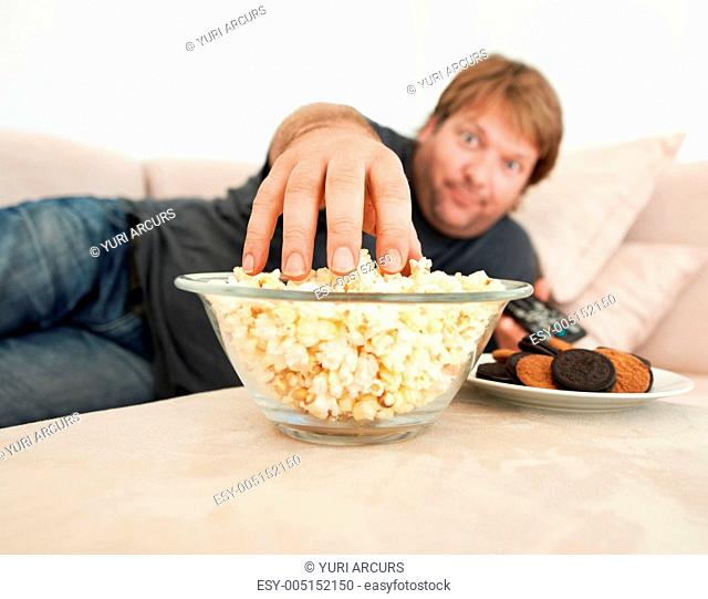 A mature man lying on the couch reaching for popcorn on the table in front of him