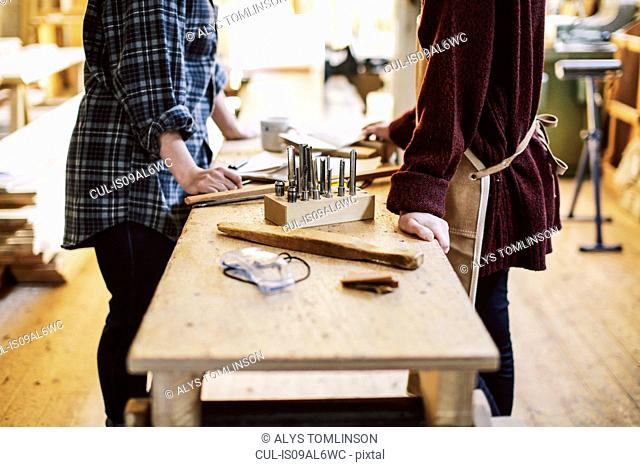 Cropped view of two craftswomen at workbench in pipe organ workshop