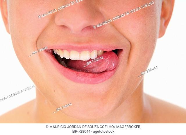 Young woman licking her lips, closeup