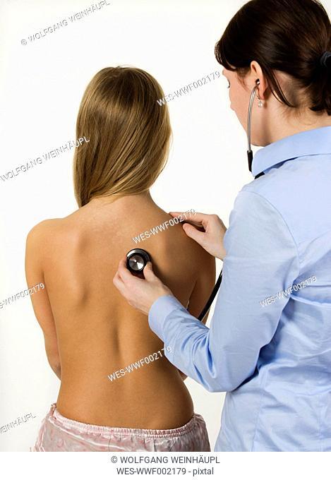 Female doctor examining teenage girl with stethoscope