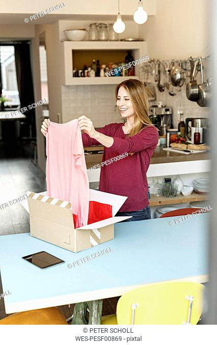 Smiling young woman at home unpacking parcel with clothing