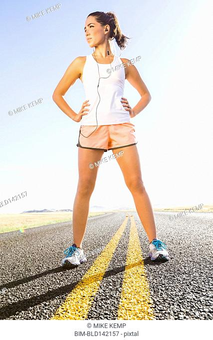 Caucasian runner standing on remote road