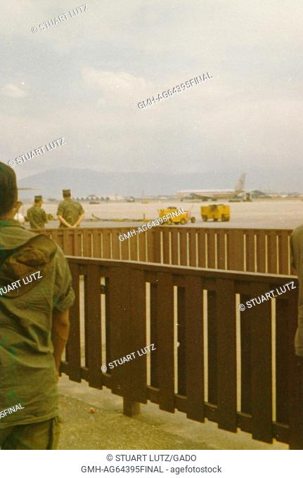 Soldiers standing by a short, wooden fence, airplane visible in the background, Danang Airport, Vietnam, 1964