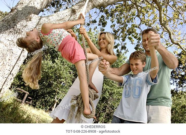 Mid adult woman swinging her daughter on a rope swing with her husband and son playing beside her