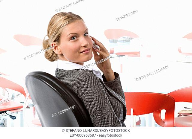 Beautiful business woman talking on the phone in a conferemce room, waiting the meeting beginning