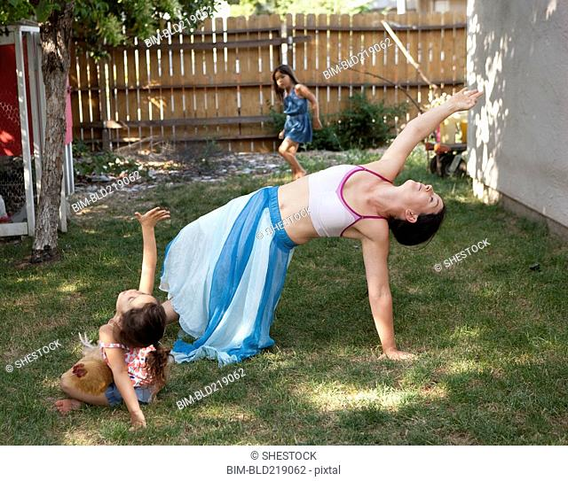 Mother and daughter dancing in backyard