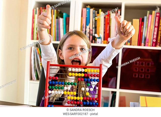 Portrait of cheering girl sitting behind abacus showing thumbs up