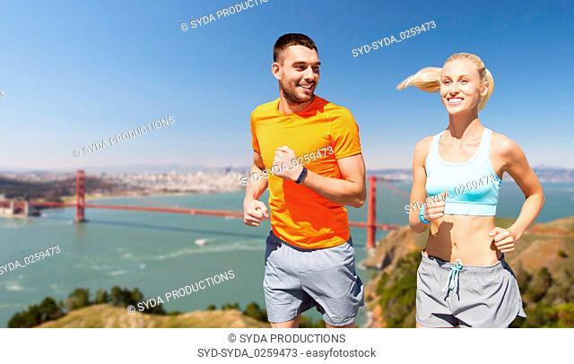 happy couple running over golden gate bridge
