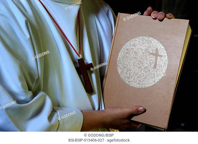 Catholic mass. Altar boy with Holy Bible. France