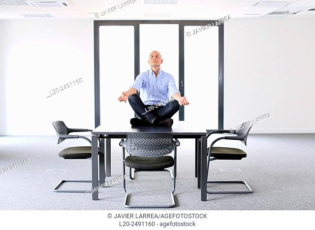 Executive doing Yoga. Empty office. Meeting room