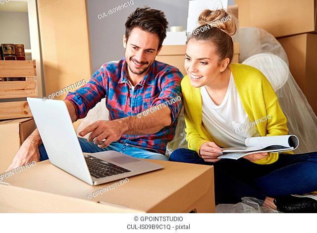 Young couple at home, surrounded by cardboard boxes, looking at laptop