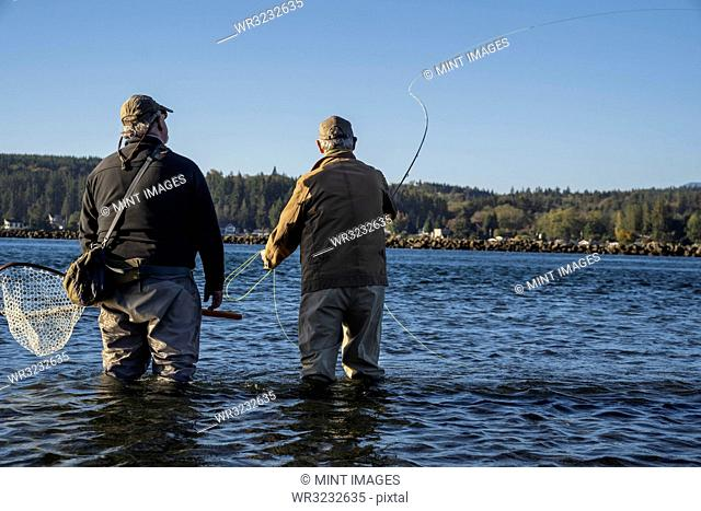 A guide advises his client while fly fishing in salt water for searun coastal cutthroat trout and salmon in northwest Washington State, USA